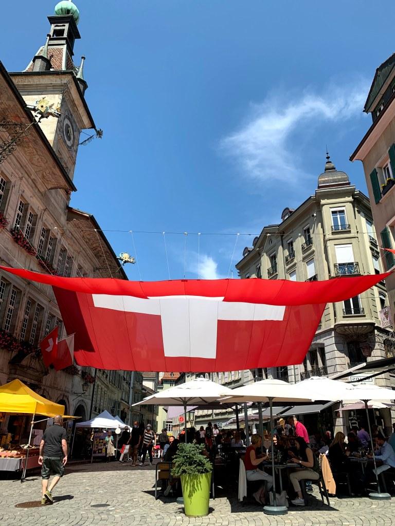 Gambar bendera Swiss di tengah plaza di kota Lausanne